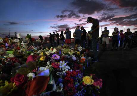 Antonio Basco stands silently at his wife's cross as family members visit the memorial site at dusk on Aug. 17 after funeral services that day for Walmart mass shooting victim Margie Reckard. Wire/TNS)