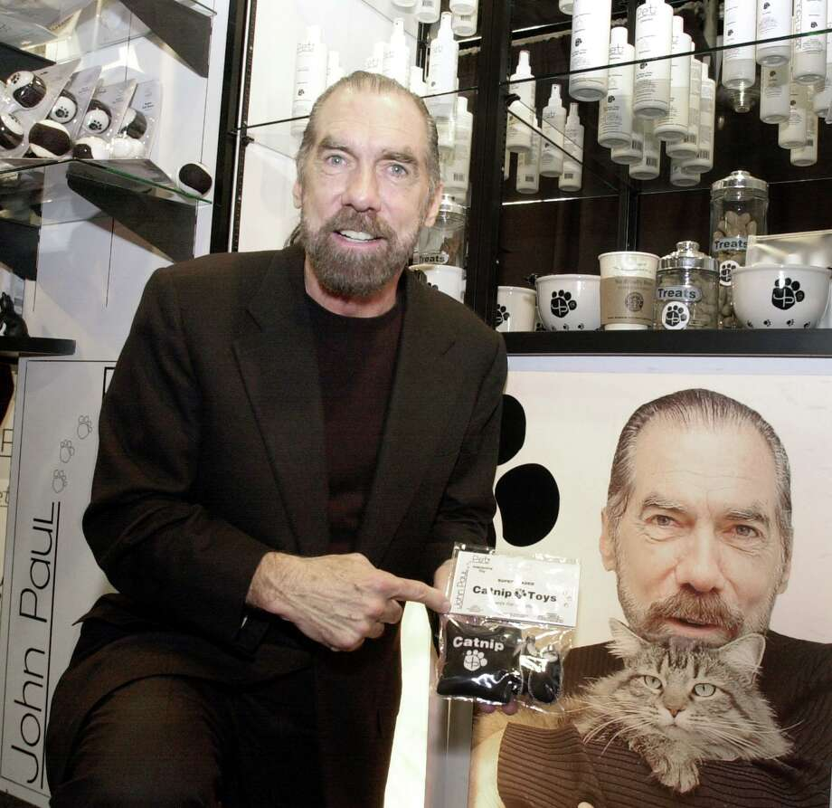John Paul DeJoria stands by a poster showing him with his cat Knucklehead as he shows off some of his John Paul Pet products at his booth at the American Pet Products Manufacturers Association Annual Pet Products Trade Show in 2003. Photo: RIC FELD, STF / AP / AP
