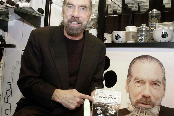 John Paul DeJoria stands by a poster showing him with his cat Knucklehead as he shows off some of his John Paul Pet products at his booth at the American Pet Products Manufacturers Association Annual Pet Products Trade Show in 2003.