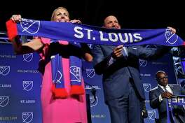 Carolyn Kindle Betz, a member of the ownership group of the new soccer franchise, and Major League Soccer Commissioner Don Garber display a St. Louis soccer scarf after the announcement, Tuesday, Aug. 20, 2019 in St. Louis. Major League Soccer has awarded the next expansion franchise to St. Louis, where a new downtown stadium will be built and the team will begin play during the 2022 season.