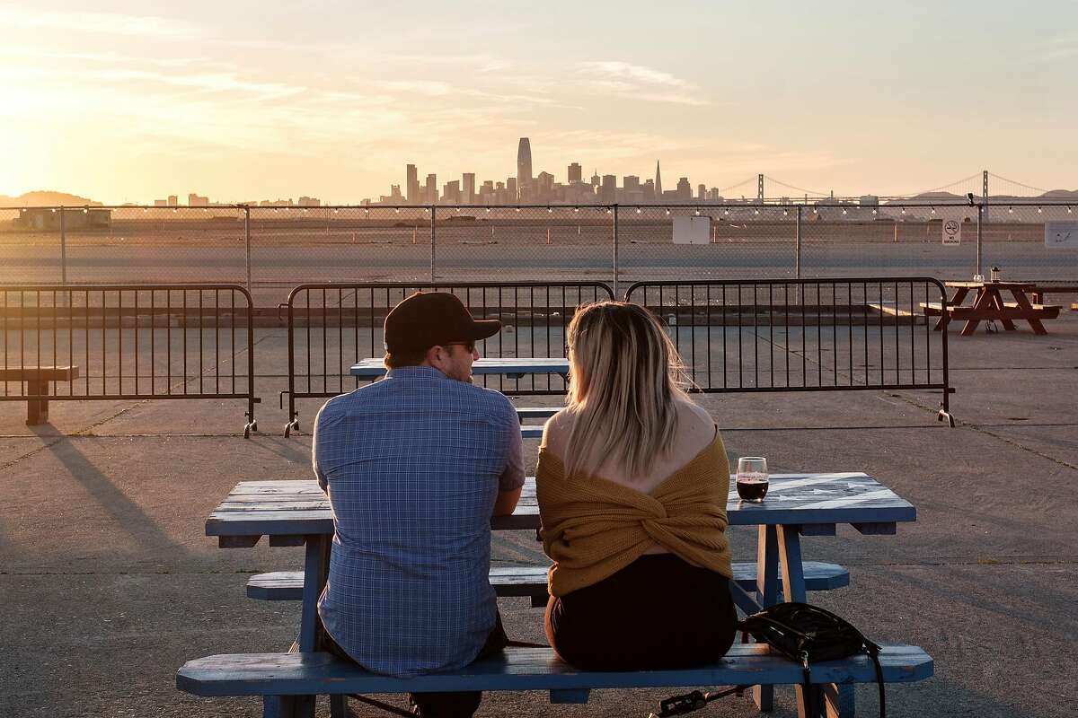Guests Joe Wescott and Kristyn Kuzniar take in the San Francisco skyline during sunset on the patio at Rockwall Winery in Oakland, Calif, on Friday, February 22, 2019.
