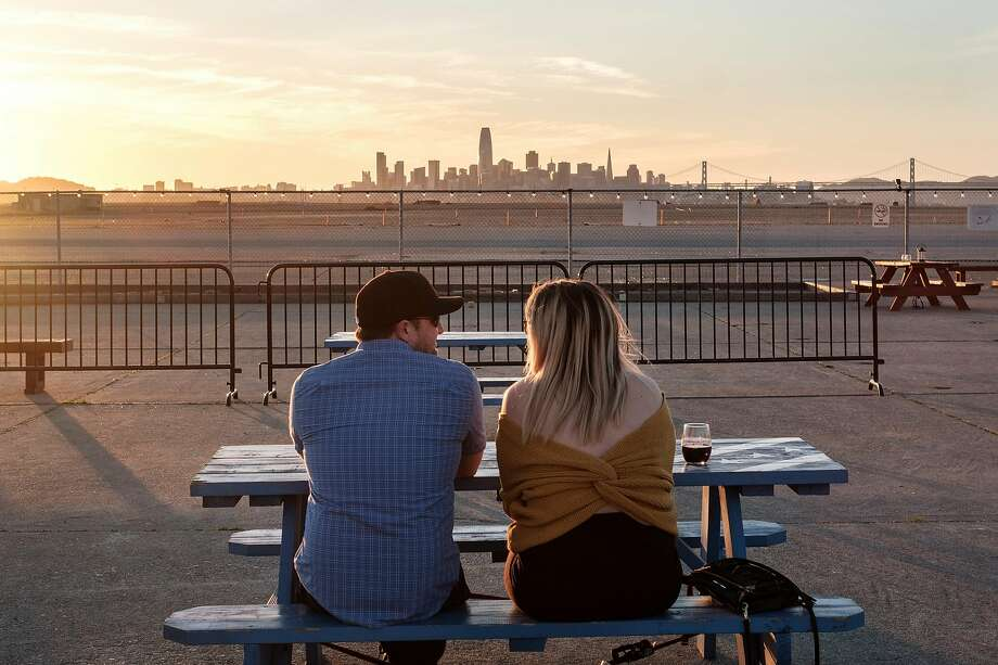 Joe Wescott and Kristyn Kuzniar take in the San Francisco skyline during sunset on the patio at Rock Wall Wine Co. Photo: Michael Short / Special To The Chronicle