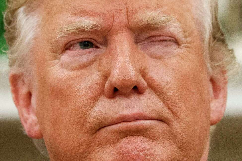 President Donald Trump winks at a journalist while speaking during a meeting with Romanian President Klaus Iohannis in the Oval Office of the White House, Tuesday, Aug. 20, 2019, in Washington. (AP Photo/Alex Brandon)