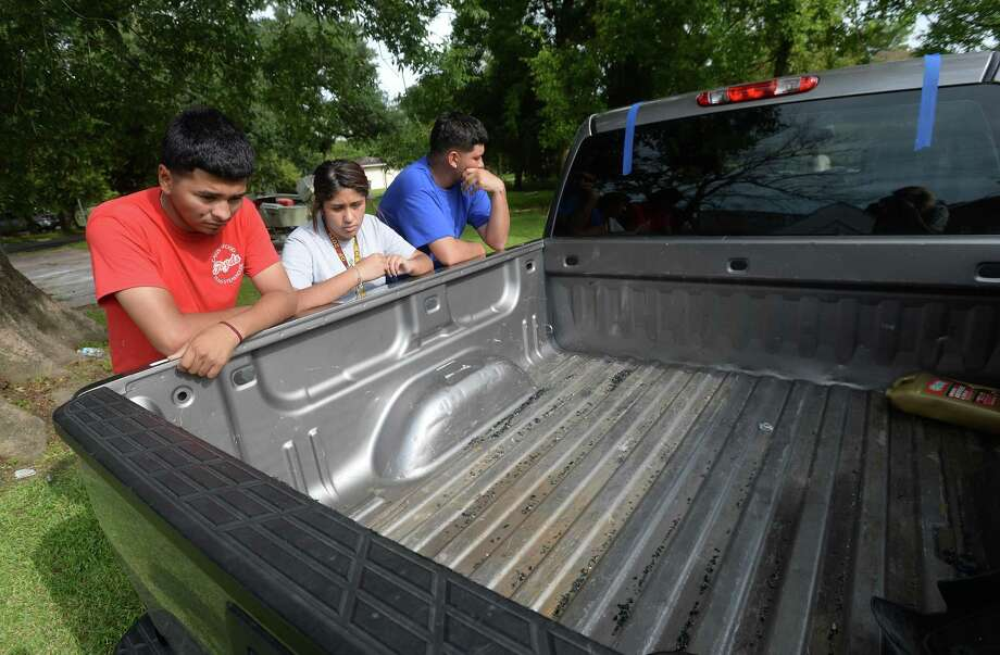 Hosvaldo Rodriguez, 19, (left) and Britney Arvizu stare down into the bed of the truck belonging to Hosvaldo's cousin, Jesse Angel Rodriguez, who was fatally shot Saturday night following an incident at Cicis Pizza near Eastex Freeway. Pieces of broken glass and the tape from rear window replacement remained in the truck bed. Members of the family and friends gathered at the family's home for a taco fundraiser to help with expenses moving forward. Hosvaldo says he and Jesse were very close, attending school together at West Brook and often hanging out and working on renovating cars, and even working together at a local rebar business. Three suspects have now been arrested and charged in the incident. 