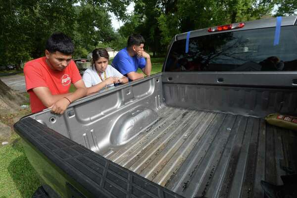 Hosvaldo Rodriguez, 19, (left) and Britney Arvizu stare down into the bed of the truck belonging to Hosvaldo's cousin, Jesse Angel Rodriguez, who was fatally shot Saturday night following an incident at Cicis Pizza near Eastex Freeway. Pieces of broken glass and the tape from rear window replacement remained in the truck bed. Members of the family and friends gathered at the family's home for a taco fundraiser to help with expenses moving forward. Hosvaldo says he and Jesse were very close, attending school together at West Brook and often hanging out and working on renovating cars, and even working together at a local rebar business. Three suspects have now been arrested and charged in the incident. Photo taken Tuesday, August 20, 2019 Kim Brent/The Enterprise