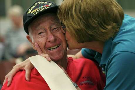 Alamo Honor Flights volunteer Elizabeth Montalvo kisses World War II veteran E.W. King, 94, before a ceremony at Joint Base San Antonio-Fort Sam Houston, Tuesday, Aug. 20, 2019. WWII veterans who weren't able to fly to France for the 75th anniversary of D-Day, were honored at the ceremony.