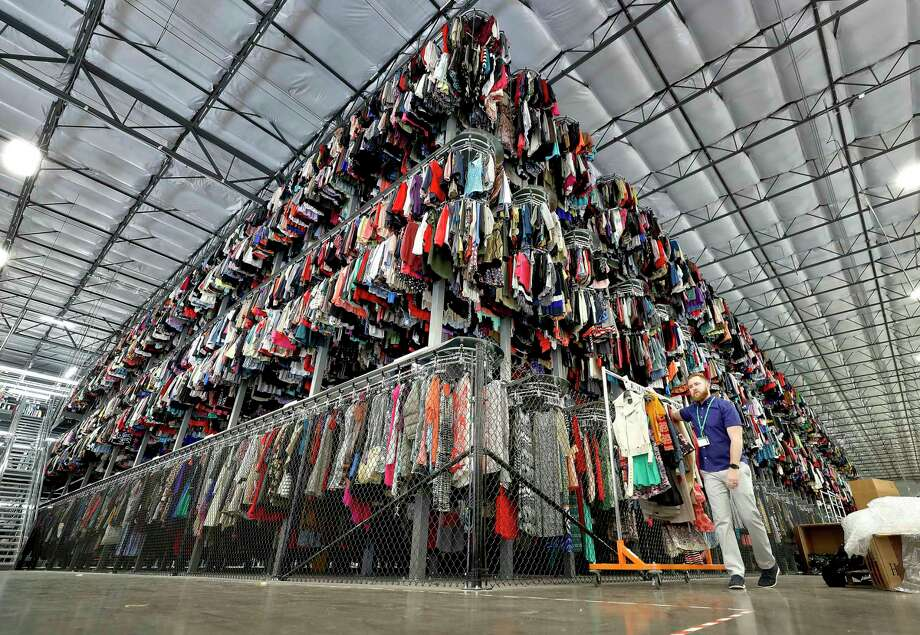 FILE - In this March 12, 2019, file photo thousands of garments are stored on a three-tiered conveyor system at the ThredUp sorting facility in Phoenix. J.C. Penney and Macy's are in the midst of rolling out a few dozen ThredUp branded shops each in time for the back-to-school shopping season. The partnerships follow a similar deal with department store retailer Stage Stores. (AP Photo/Matt York, File) Photo: Matt York / Matt York / Associated Press / Copyright 2019 The Associated Press. All rights reserved.