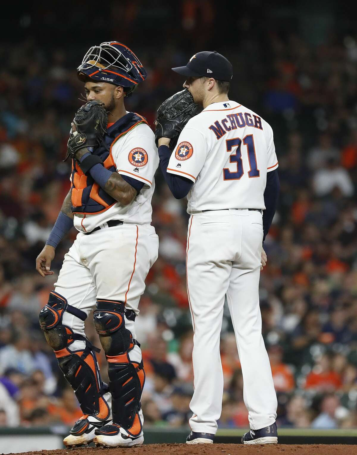Houston Astros relief pitcher Collin McHugh (31) chats with catcher Martin Maldonado (12) during the sixth inning of an MLB game at Minute Maid Park, Tuesday, August 20, 2019.