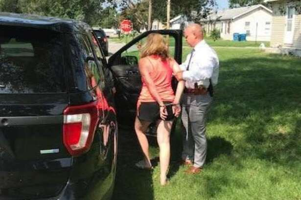 Wood River police on Monday take Kelly Hart into custody.