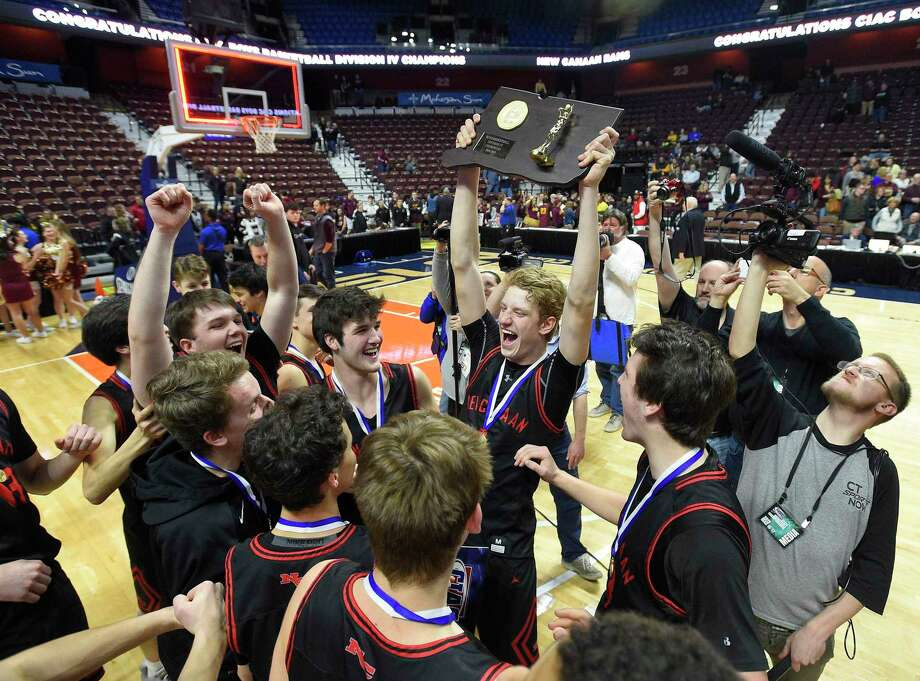 New Canaan celebrates with the championship plaque after defeating Granby 55-39 in the CIAC Div. IV final at Mohegan Sun Arena in Uncasville on March 16. Photo: Matthew Brown / Hearst Connecticut Media / Stamford Advocate