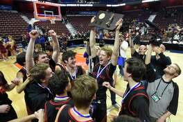 New Canaan celebrates with the championship plaque after defeating Granby 55-39 in the CIAC Div. IV final at Mohegan Sun Arena in Uncasville on March 16.