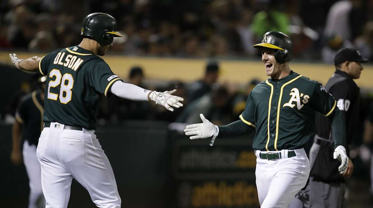 Oakland Athletics' Mark Canha, right, celebrates with Matt Olson (28) after scoring against the New York Yankees during the sixth inning of a baseball game Tuesday, Aug. 20, 2019, in Oakland, Calif. (AP Photo/Ben Margot)