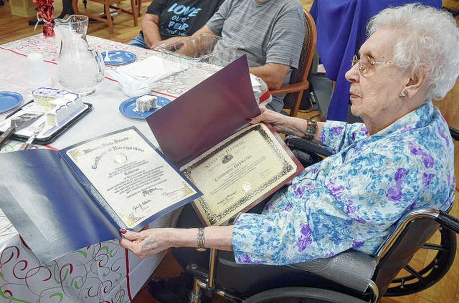 Catherine DeFrates, 103, looks at the state Senate and House resolutions honoring her as a Woman of Wisdom. DeFrates lives at Heritage Health. Photo: Marco Cartolano | Journal-Courier