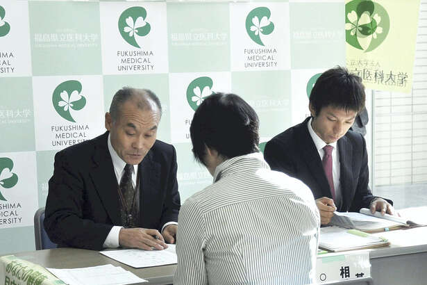 Officials of Fukushima Medical University instruct a resident on how to fill in a questionnaire sheet for the health survey of prefectural residents at the Fukushima city government office in November 2012.