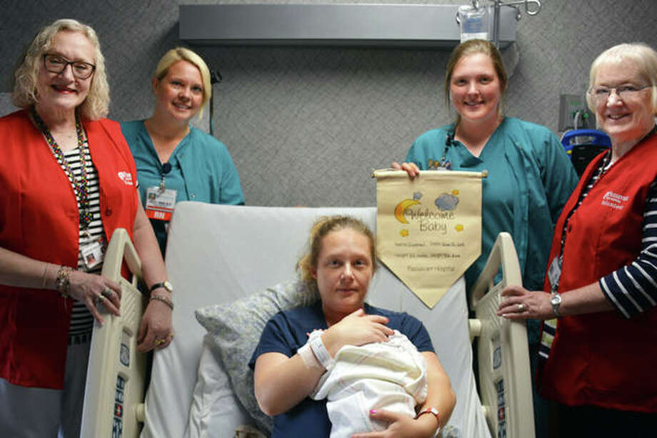 """The Passavant Area Hospital Auxiliary is now giving special """"Welcome Baby"""" banners to new parents to take home. Angela Moore (center) and Jason Elliott, parents of Gunner Ray Elliott, were the first recipients and presented a banner by Barb Hansmeier (from left) of the Passavant Auxiliary; nurse Simone Parlier; nurse Jessica Yost; and Passavant Auxiliary member Debbie Richards. Photo: Photo Provided"""