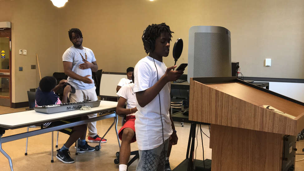 Nykale Burbridge, standing at right, records a rap song in the'Mic Drop' program at Albany Public Library's Howe Branch, overseen by Ozymandias Merci Morris, rear. Seated are Chance Bradford, left, James Kitchen, rear, and Jahleim Holmes, red shorts at right (photo by Amy Biancolli)
