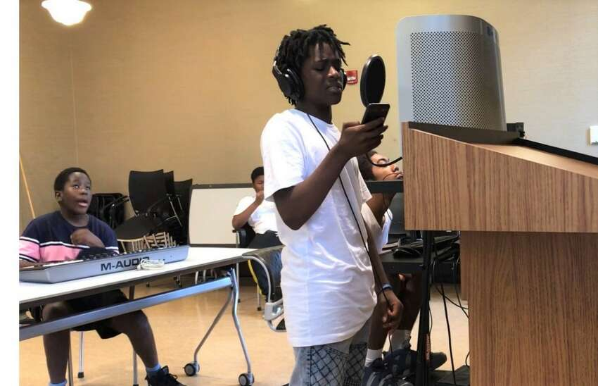 Nykale Burbridge records a rap song with the 'Mic Drop' program at the Albany Public Library Howe Branch (photo by Amy Biancolli)