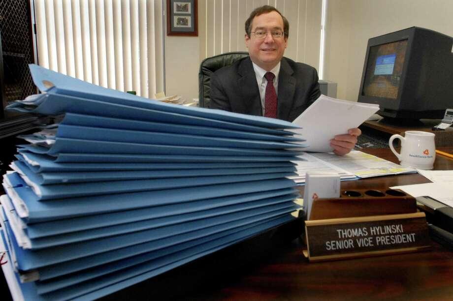 Alliance Bank Senior Vice President, Thomas Hylinski, withrefinancing paperwork. Melanie Stengel/Register