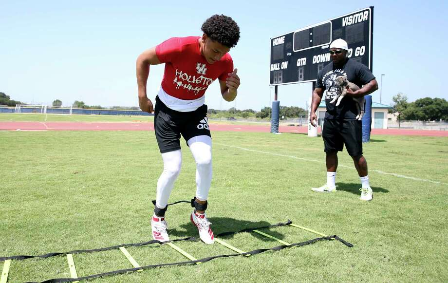 Jordan Battles works out on the ladder with the coaching of his dad. Photo: Tom Reel / 2019 SAN ANTONIO EXPRESS-NEWS
