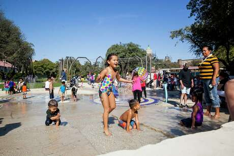 Alyssa Gonzales, 7, plays in the splash pad with her brother, Xander, 4, at the opening ceremony of Yanaguana Garden Saturday Oct. 3, 2015 at Hemisfair.