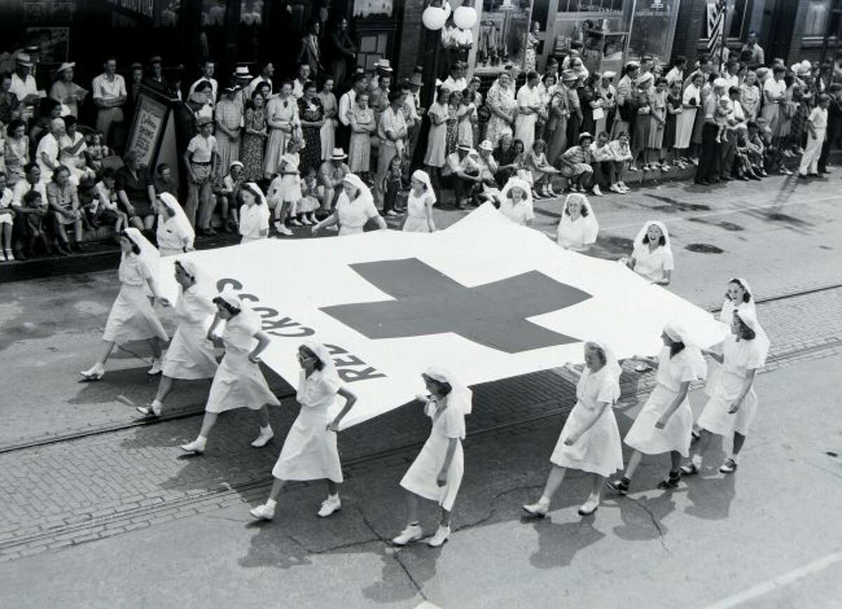 A group of Red Cross workers hold the Red Cross flag as they march down River Street during the Fourth Annual Manistee National Forest Festival Parade on July 4, 1939.