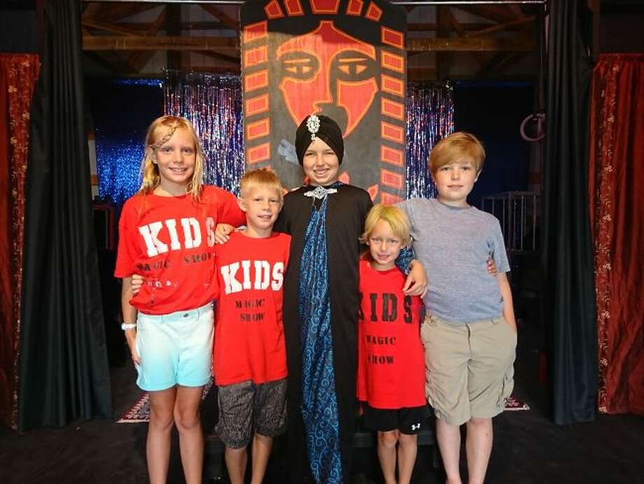 """Pictured (from left to right): Aria Grossenbach, Lennon Grossenbach, Micheal Sager Wissner, Oscar Grossenbach and Anthony Sager Wissner. The young magicians are standing in front their """"mummy case"""" illusion. (Ashlyn Korienek/News Advocate)"""