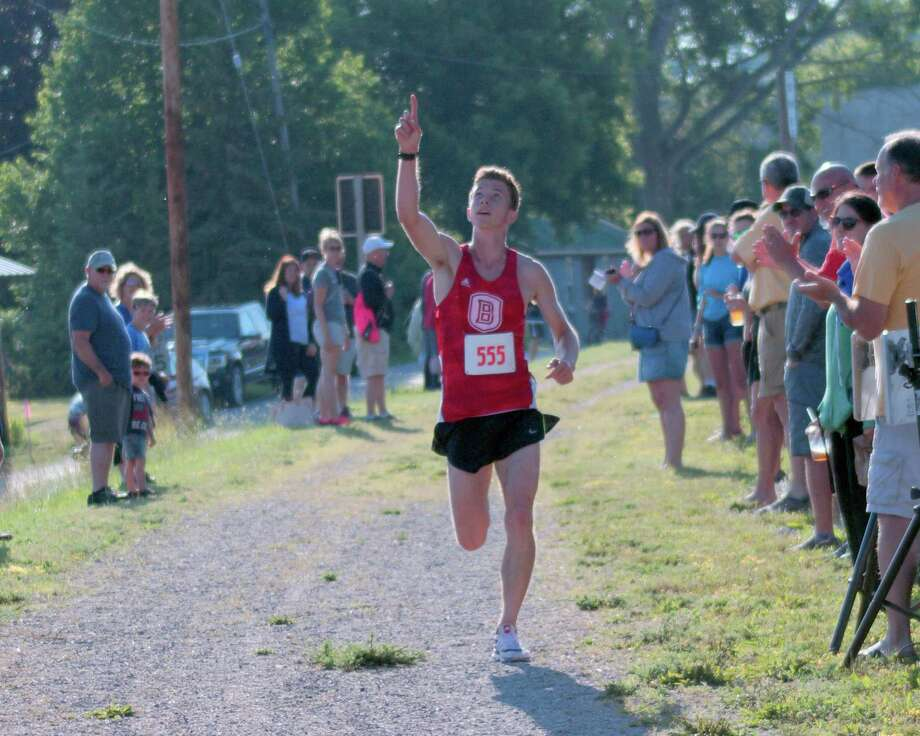 """Benzie Central alumnus Brayden Huddleston says, """"This one's for Coach Moss,"""" as he dedicates his Firecracker 5k victory to legendary Benzie Central cross country and track coach Eldon """"Pete"""" Moss, who passed away earlier this year. (Courtesy photo)"""