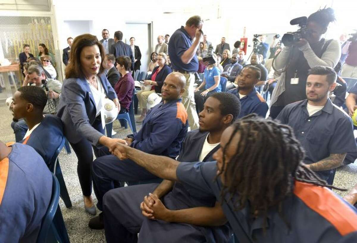 Michigan Governor Gretchen Whitmer shakes hands with inmates in the tree trim training program after she speaks at the Parnell Vocational Village, Tuesday, July 9, 2019, in Jackson, Mich. DTE Energy and Michigan's prison system have launched a tree-trimming program that aims to fill open jobs and find full-time employment for released inmates. State, utility and union officials announced the program Tuesday at the Parnall Correctional Facility in Jackson. (Todd McInturf/Detroit News via AP)