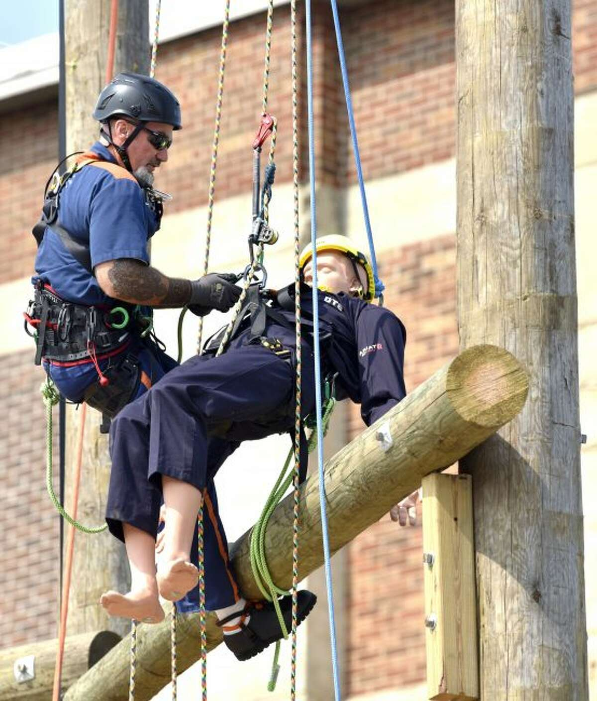 Inmate student Jeffrey Gunnells prepares to rescue this mannequin during a demonstration Tuesday, July 9, 2019, in Jackson, Mich. DTE Energy and Michigan's prison system have launched a tree-trimming program that aims to fill open jobs and find full-time employment for released inmates. State, utility and union officials announced the program Tuesday at the Parnall Correctional Facility in Jackson. (Todd McInturf/Detroit News via AP)