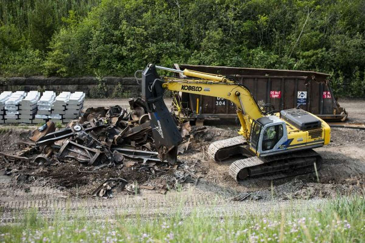 In this Monday morning, July 8, 2019, a work crew removes debris from a June 28, freight train derailment in Port Huron, Mich. The international train tunnel connecting Michigan's Port Huron to Sarnia, Ontario, has been cleared and repaired following the multi-car train derailment that spilled sulfuric acid and damaged the tracks. (Brian Wells/The Times Herald via AP)