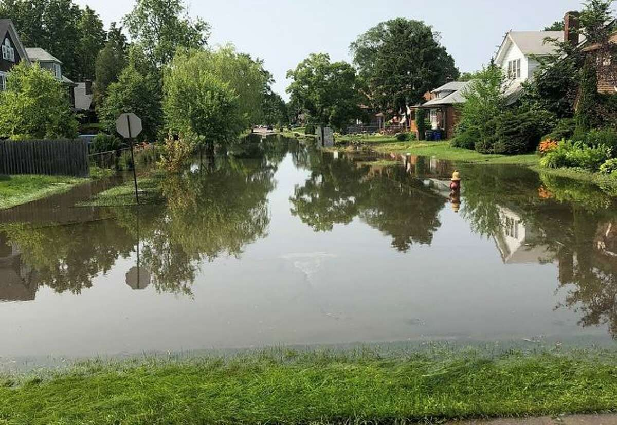 In a July 9, 2019 photo, Detroit River and canal water pouring over and through seawalls is flooding streets, homes and basements on Detroit's east side. The U.S. Army Corps of Engineers says three months of abnormally wet weather have kept stream flows into the Great Lakes well above average. Thousands of sandbags are expected to be placed along streets and in yards near Detroit River canals to keep water from flooding homes and basements. (AP Photo/Corey Williams)