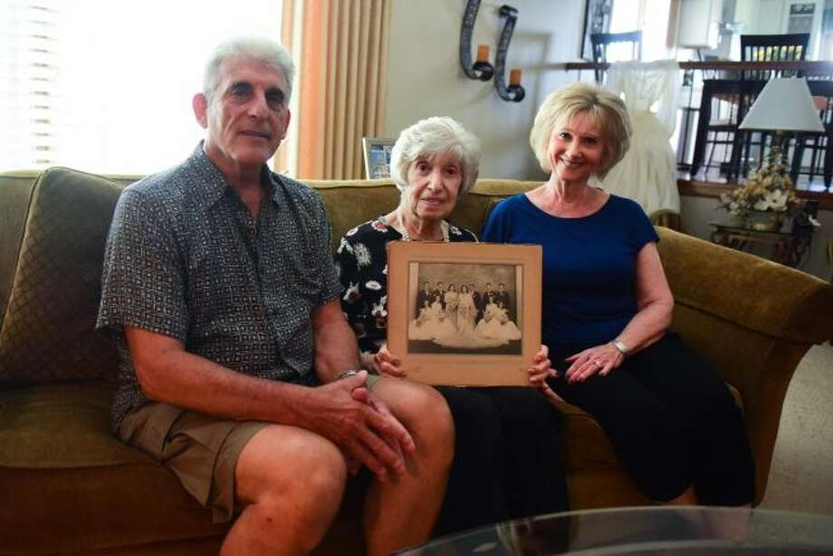Edith Bonsonto, holding her wedding photo, sits with her son Gerald and her daughter-in-law Caroline. Her wedding dress was made from her late husband's WWII parachute. Thursday, June 27, 2019, in Orland Park. (Gary Middendorf/Daily Southtown/TNS)