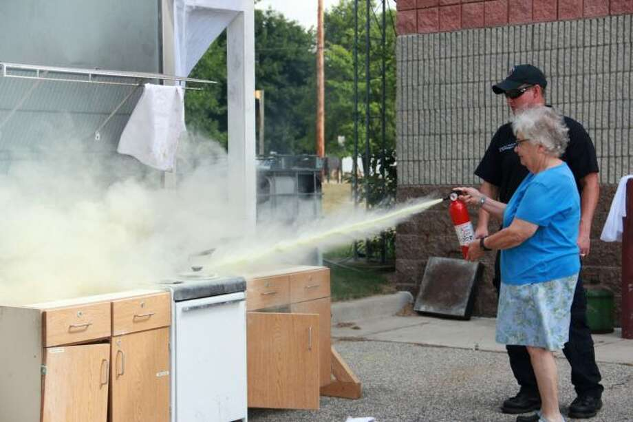 Camp 911 guest Rebecca Robb takes her turn using a fire extinguisher. During the camp, all seniors learned how to put out their own kitchen fires during this fire safety presentation. (Pioneer photo/Alicia Jaimes)