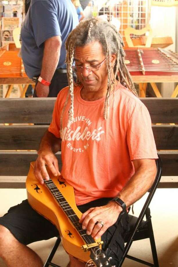 Bing Futch plays the mountain dulcimer in front of his vendor booth. He is one of Friday evening's performers. (Pioneer photo/ Catherine Sweeney)