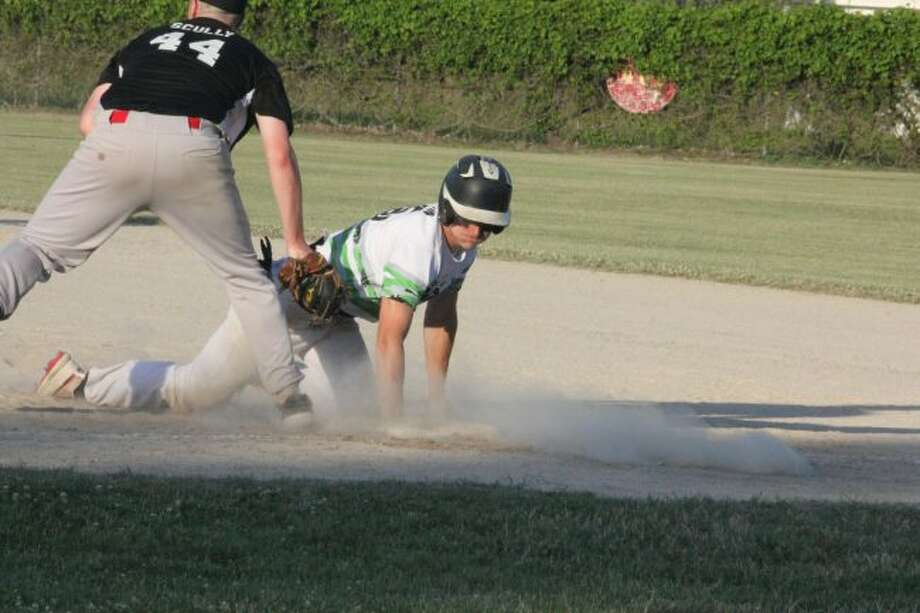 Reed City's Payton Hansen dives safely back into first base in Sunday's 18U title game at Win Kellum Field for the Quad City Storm. (Pioneer photo/John Raffel)