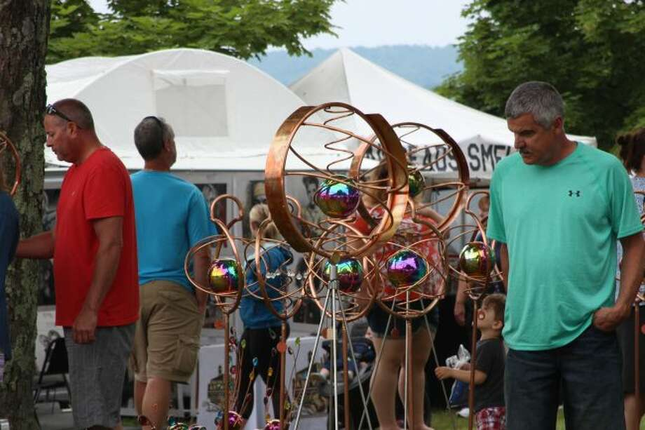 A visitor at the Beulah Art Fair looks at unique lawn sprinklers displayed in Beulah Village Park (Photo/Colin Merry)