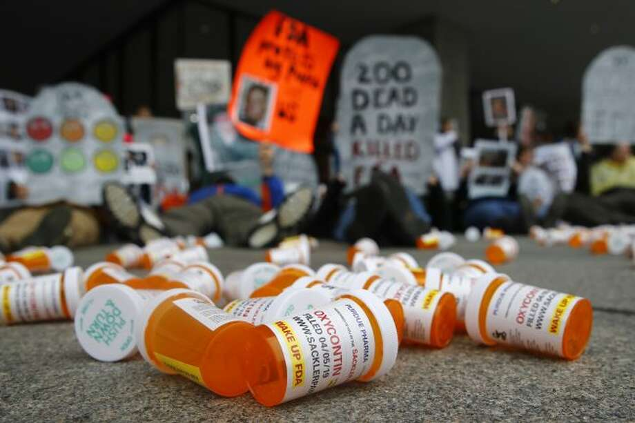 FILE - In this April 5, 2019, file photo, containers depicting OxyContin prescription pill bottles lie on the ground in front of the Department of Health and Human Services' headquarters in Washington as protesters demonstrate against the FDA's opioid prescription drug approval practices. (AP Photo/Patrick Semansky, File)