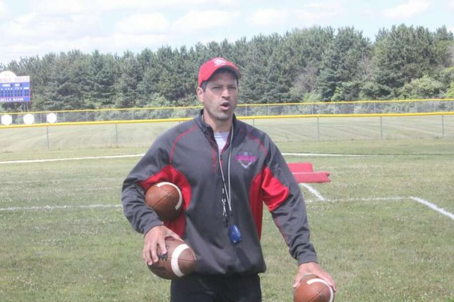 Chippewa Hills assistant coach Ryan Grinnell collects footballs after a Warrior camp practice on Monday. (Pioneer photo/John Raffel)