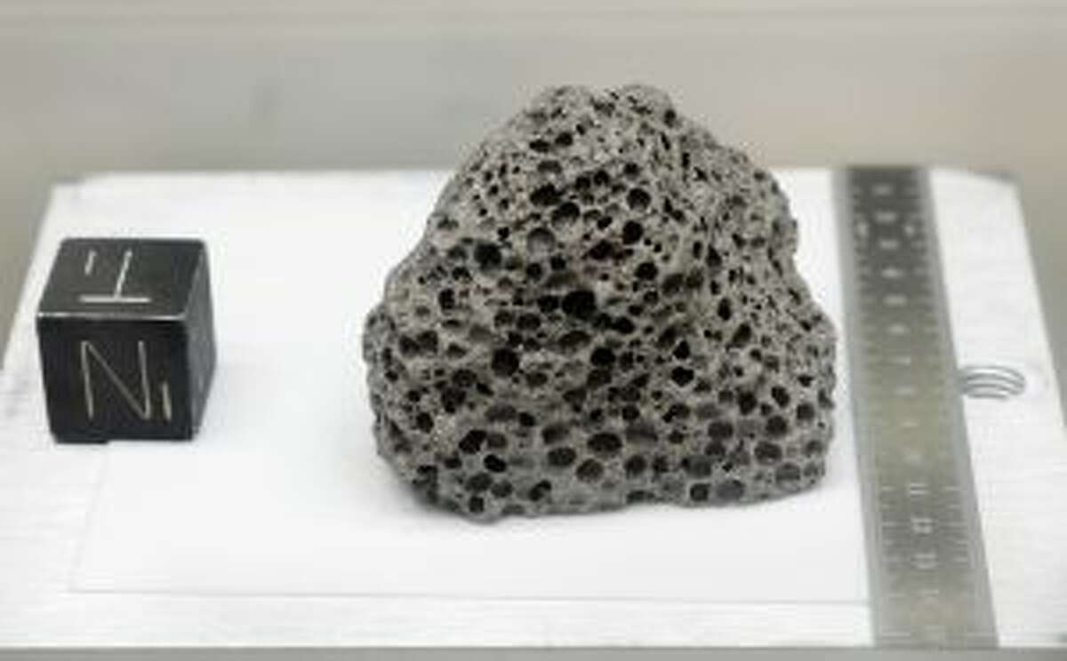 Collected during Apollo 15, a 3.5 billion years old basalt rock similar to rocks formed around Hawaii, is displayed in a pressurized nitrogen-filled examination case inside the lunar lab at the NASA Johnson Space Center Monday, June 17, 2019, in Houston. For the first time in decades, NASA is about to open some of the pristine samples and let geologists take a crack at them with 21st-century technology. (AP Photo/Michael Wyke)