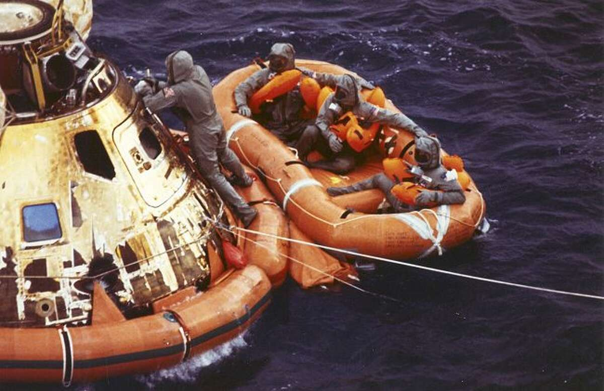 FILE - In this July 24, 1969 photo from the U.S. Navy, Lt. Clancy Hatleberg closes the Apollo 11 spacecraft hatch as astronauts Neil Armstrong, Michael Collins, and Buzz Aldrin, Jr., await helicopter pickup from their life raft after splashdown in the Pacific Ocean, 900 miles southwest of Hawaii, returning to Earth from a successful lunar landing mission. His mission was to decontaminate the astronauts and their command module, Columbia, immediately following splashdown. (Milt Putnam/U.S. Navy via AP)