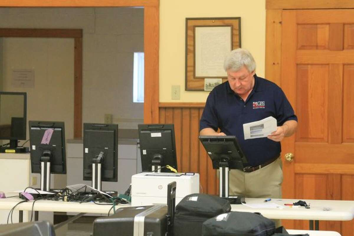 Kurt Knowles, account manager for Governmental Business Systems checks a touchscreen voting machine at Brown Township Hall. (Scott Fraley/News Advocate)