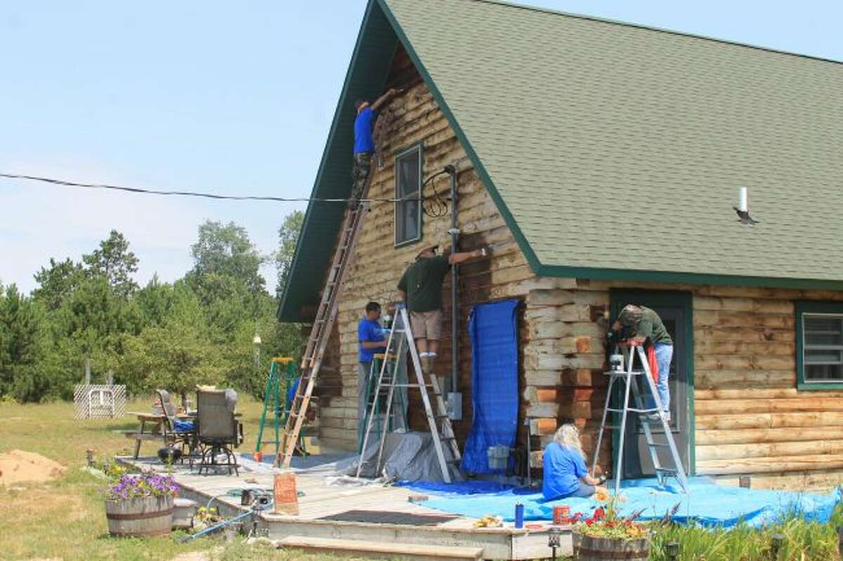 Workers from the Kaleva Bible Church refinish a log cabin during their 'Beyond KBC Walls' community work event. (Scott Fraley/News Advocate)