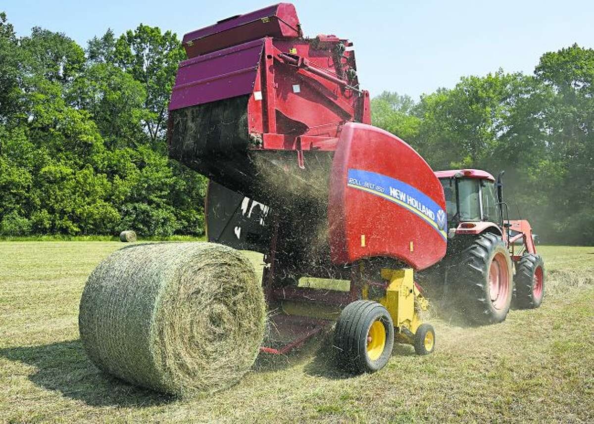 Cutline: Joe Stewart operates a baler in an Oktibbeha County, Mississippi, hayfield Aug. 23, 2018. (Photo by MSU Extension Service/Kevin Hudson)Alt Text: A red baler hitched to the back of an orange tractor drops a new, round bale of hay into a field.
