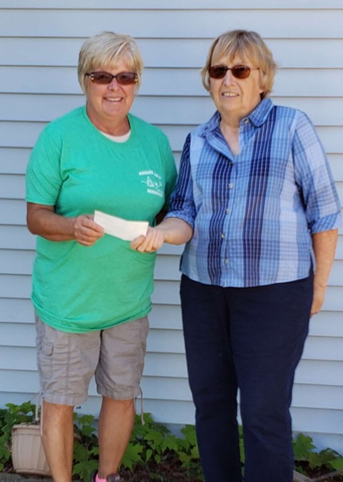 Terri Schmidt, of Peasanton Valley Greenhouse, presents a check to Marian Jarvinen, president of Friends of the Manistee County Library, from the proceeds of a recent fundraiser. Bob and Terri Schmidt are avid supporters of the Manistee County libraries. The donation will support programs like the Children's Summer Reading Program and other needs as they arise. (Courtesy photo)