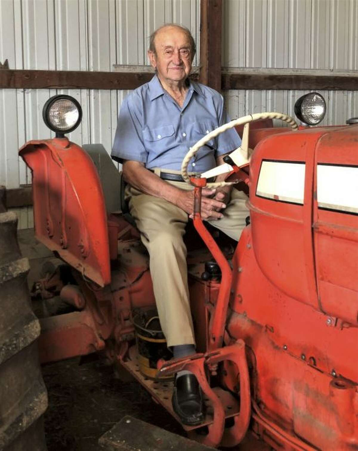 Farmer Leonard Sauer, sits on a red Allis-Chalmers tractor that is just one of the tractors Sauer still uses to bale hay, cut grass and more in Kellnersville, Wis., Tuesday, July 16, 2019. Sauer still drives tractors at his Village View Dairy Farm in Kellnersville. In just a few weeks, he will turn 100. (Maddy McTigue/Herald-Times Reporter via AP)