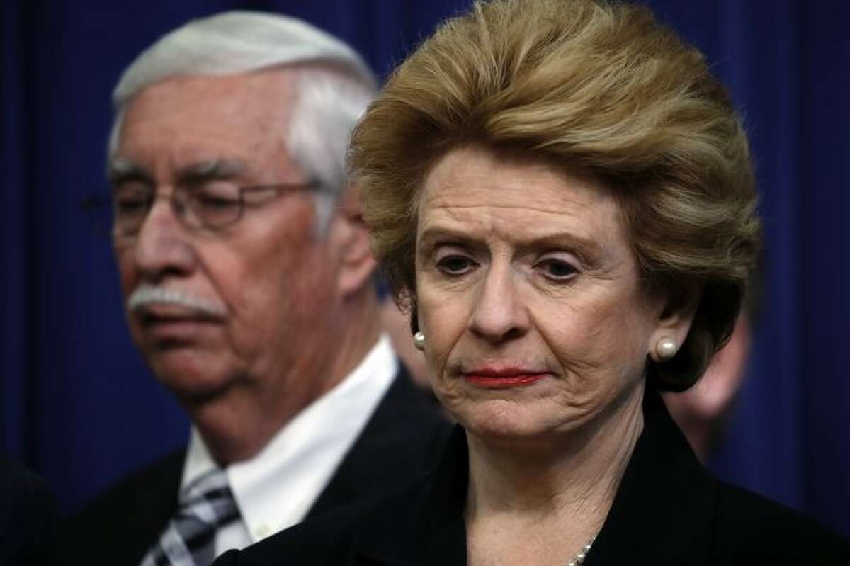 """In this Dec. 20, 2018 file photo, Sen. Debbie Stabenow, D-Mich., right, listens as President Donald Trump speaks during a signing ceremony on the White House complex in Washington. Stabenow says she would back House Democrats if they launch an impeachment inquiry against President Trump. The fourth-term Democrat said in a written statement Monday, July 29, 2019 that former special counsel Robert Mueller's report about Russian interference in the 2016 election """"describes extremely serious instances of the president of the United States trying to obstruct justice."""" She says """"no one is above the law."""" (AP Photo/Jacquelyn Martin, File)"""