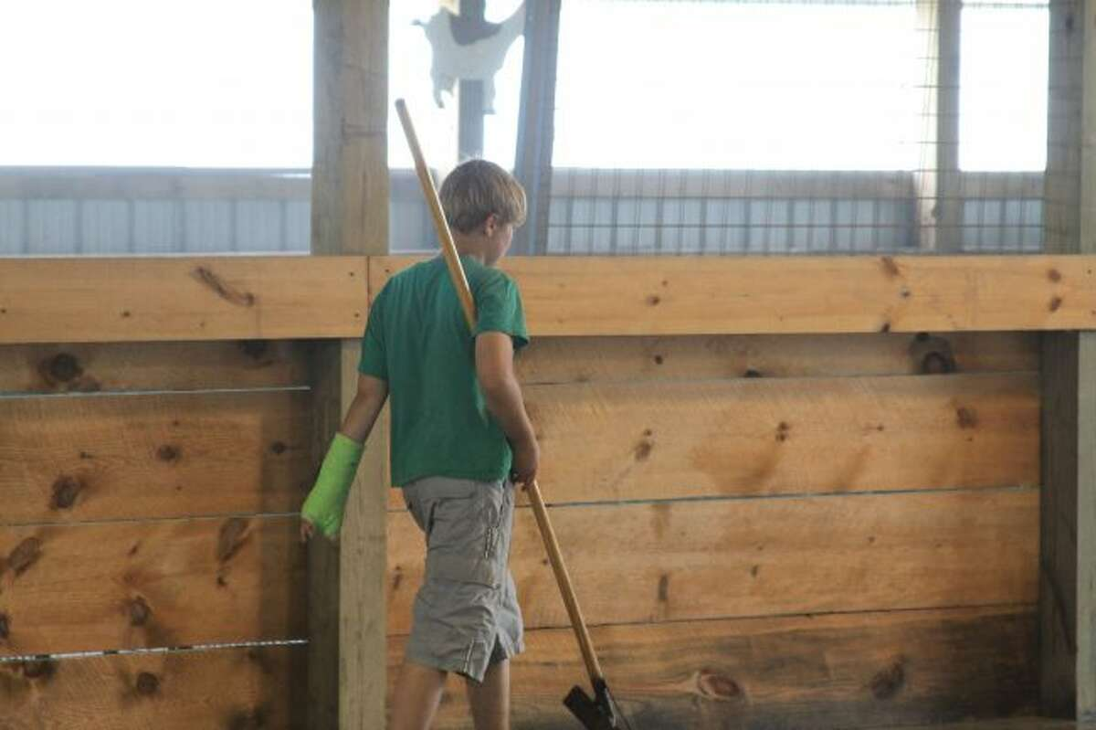 A hard-working youth puts elbow grease into cleaning flooded livestock barns at the Manistee County Fairgrounds. (Scott Fraley/News Advocate)