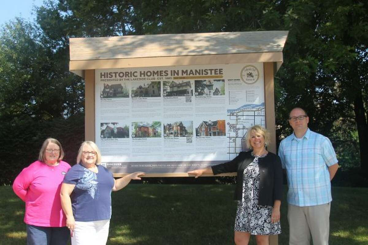 (From left) Peggy Raddatz, Lakeside Club; Deb Green, Lakeside Club president; Kathryn Kenny, Executive Director of the Manistee County Visitor's Bureau; and Mark Fedder, Manistee County Historical Museum executive director show off the new Historical Homes in Manistee display, which is located on River Street, near the Manistee Municipal Marina. (Scott Fraley/News Advocate)