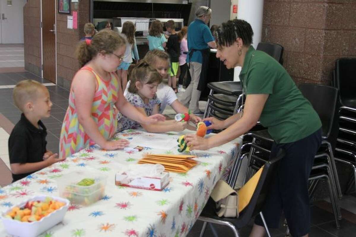 District Health Department No. 10 public health educator Holly Joseph (right) speaks with children at the Manistee Area Public Schools summer lunch program about eating healthy. The Cooking with Kids program is being supported this summer with SNAP (Supplemental Nutrition Assistance Program) education funding from the Michigan Fitness Foundation which is overseen by Michigan Department of Health and Human Services.