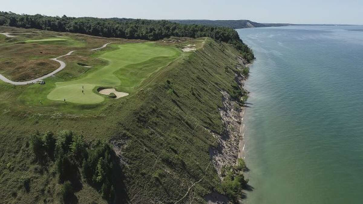 A Friday, July 13, 2019 aerial photo of Arcadia Bluffs Golf Club 12th hole green and fairway near Arcadia Township, Mich. The golf club has changed its website to no longer encourage players to hit balls into Lake Michigan after a diver hired by a newspaper found hundreds in the water. (Mandi Wright and Junfu Han/Detroit Free Press via AP)